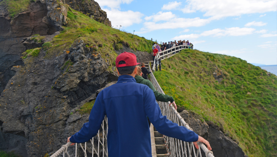 Man walking across Carrick-a-rede-rope bridge