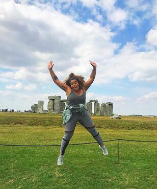 London Marketing intern Mariah jumping in front of Stonehedge
