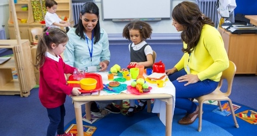 Teachers work and play with young children