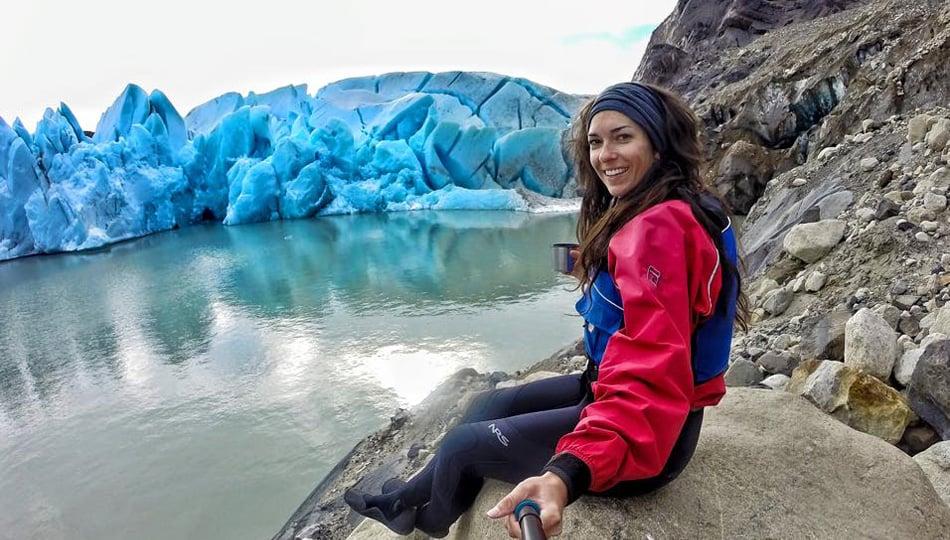 Woman sitting on a rock by a glacier