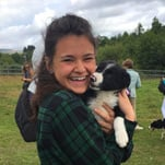 Jaclyn K. holding a black and white puppy