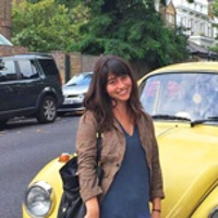 Marisa standing in front of yellow VW in the streets of London